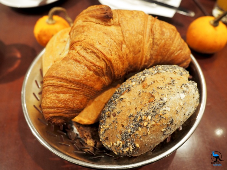 Basket of bread, including croissant and Brötchen.
